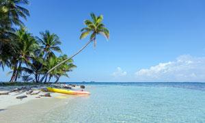 藍天下在海邊停泊的小舟攝影圖片