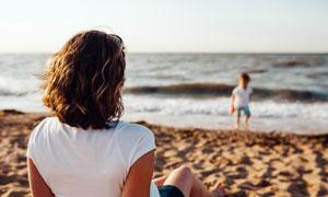 沙滩上带着孩子玩耍的妈妈摄影图片
