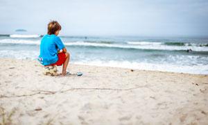 沙滩上坐在足球上的男孩摄影图片