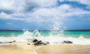海邊沙灘上濺起的浪花攝影圖片