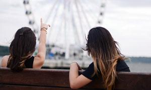 做在靠椅是手指著摩天輪的美女攝影圖片