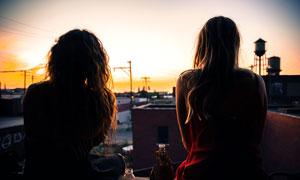 夕陽下遙看遠方的美女背景攝影圖片