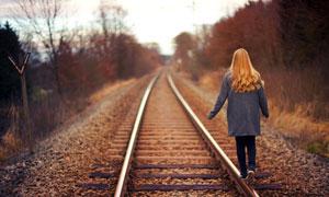 走在铁轨上的美女背影摄影图片