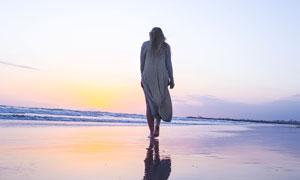 夕陽下在沙灘散步的美女攝影圖片