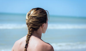 海边长辫子的美女背影摄影图片