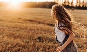 田園上奔跑的長發美女攝影圖片
