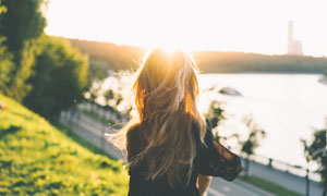 陽光下的金發美女背影攝影圖片