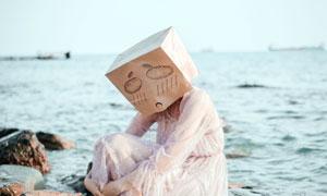 坐在石頭上帶著囧盒子的美女圖片