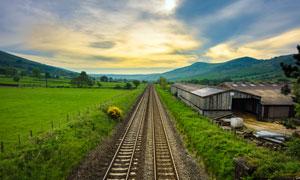 黄昏下的铁轨和草地摄影图片