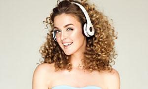 戴上耳機聽音樂的卷發美女攝影圖片