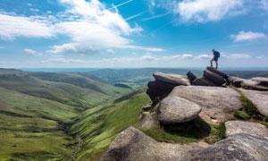 站在山顶上瞭望远方的游客摄影图片