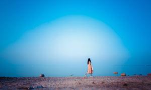蓝天下在湖边散步的美女摄影图片