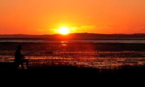 夕阳下在河边垂钓者剪影摄影图片