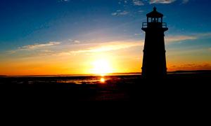 夕阳下海边美丽的灯塔剪影摄影图片