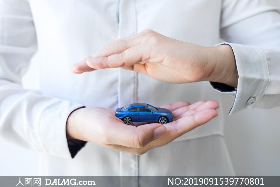 放在掌心里的蓝色汽车模型高清图片