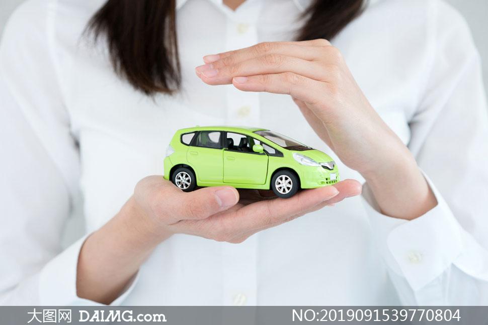 手心上的绿色汽车模型特写高清图片