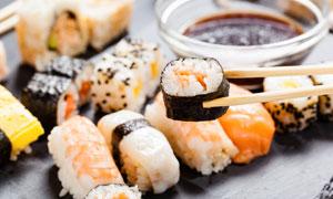 筷子夹起来的美味寿司摄影高清图片