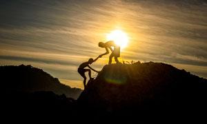 相互帮助攀登的人物剪影摄影图片
