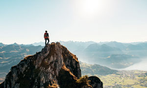 户外攀登到山顶的男人摄影图片
