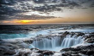 夕阳下的湖边瀑布美景摄影图片
