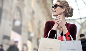 微笑著手拿著購物袋的美女攝影圖片