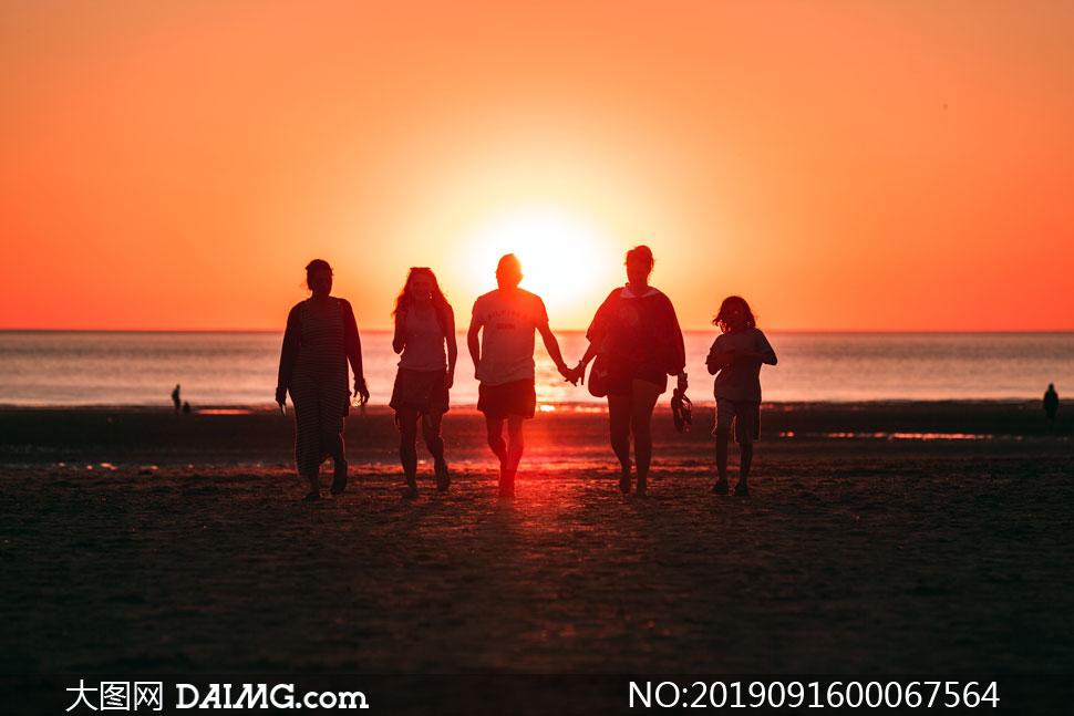 夕阳下的海边一家人剪影摄影图片