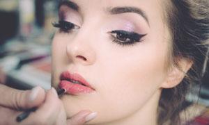 正在涂抹唇膏的美女摄影图片