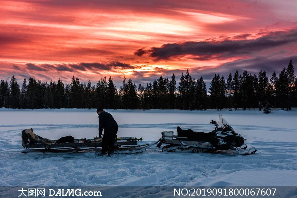 黄昏下的雪地和雪地车摄影图片