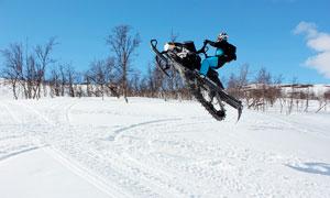 在雪地上骑着雪地车特技表演摄影图片