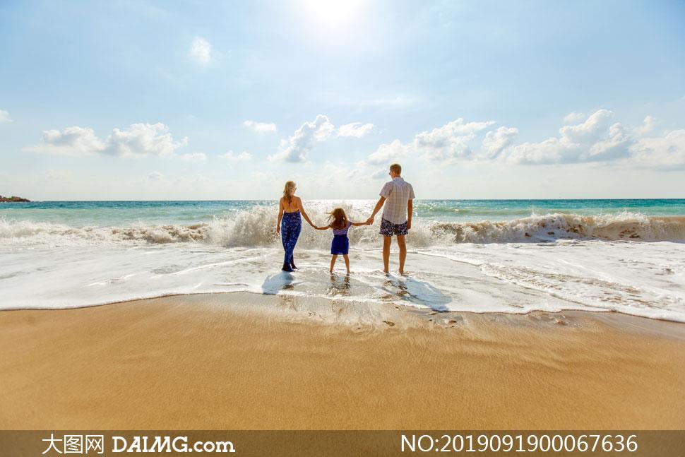 沙滩上散步的一家三口背影摄影图片