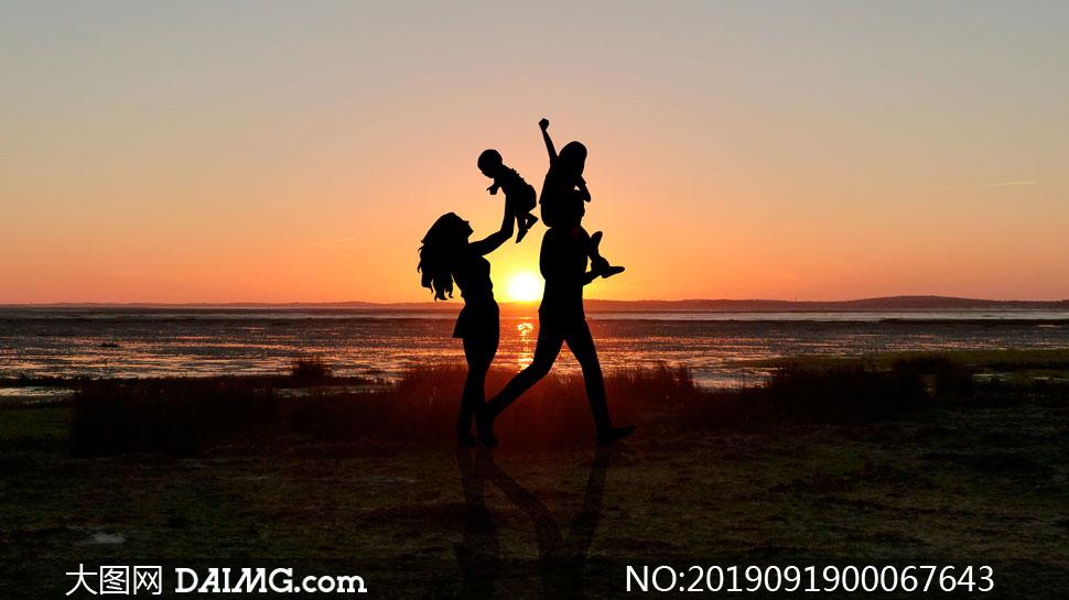 在海边散步的一家人剪影摄影图片