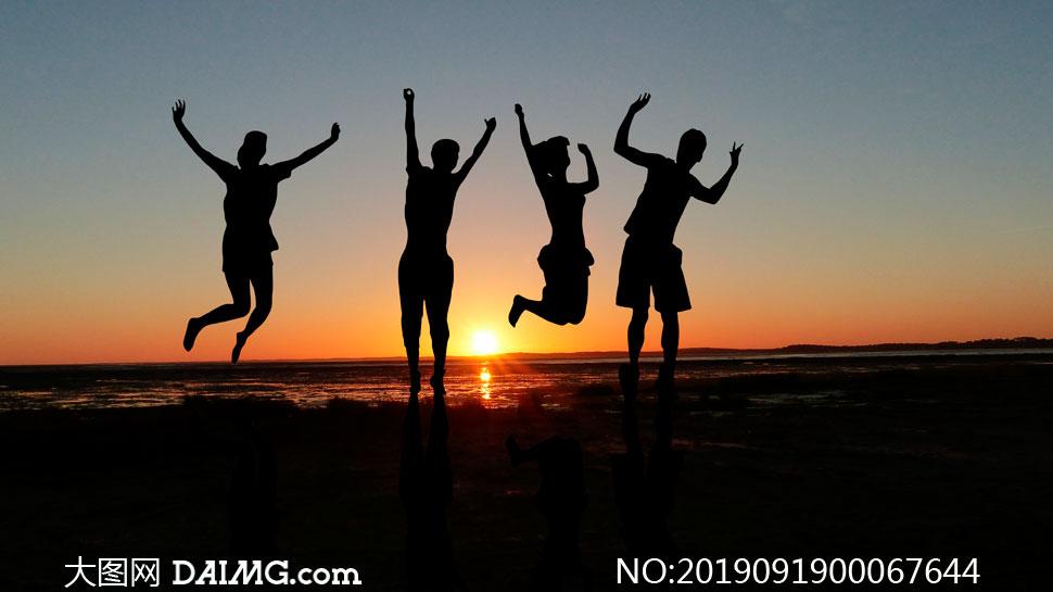 夕阳下海边跃起的人物剪影摄影图片