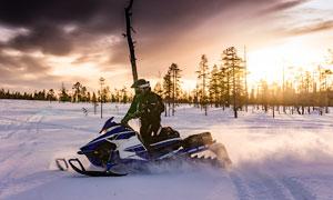 清晨在雪地上骑行雪地车场景摄影图片