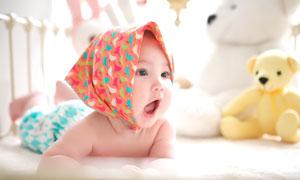 趴在床上張開嘴巴的嬰兒攝影圖片