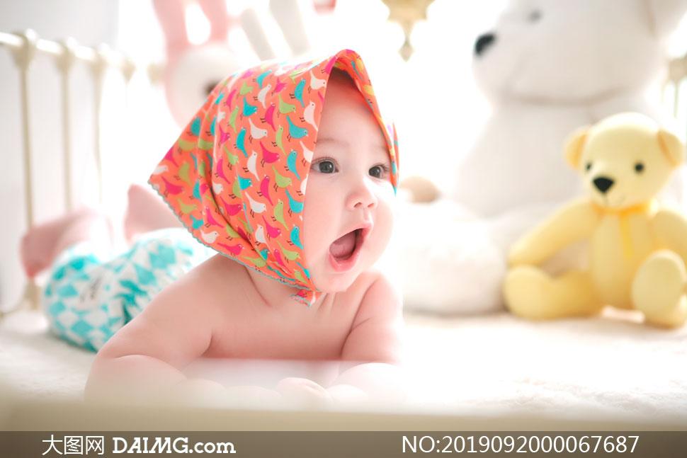趴在床上张开嘴巴的婴儿摄影图片