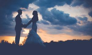 夕阳下手拉手的情侣剪影摄影图片