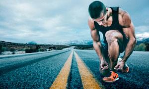 在马路上系鞋带的运动员摄影图片