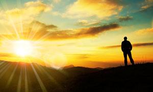 阳光下站在山顶上的人物剪影摄影图片