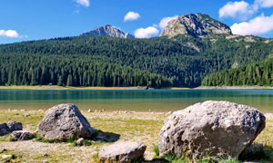 山林下的湖泊和石头摄影图片