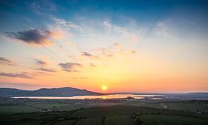 落日下的河流和田園風光攝影圖片