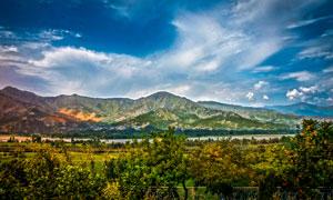 蓝天白云下的山川和树木摄影图片