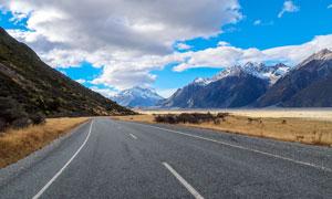 蓝天白云下的山脚公路摄影图片