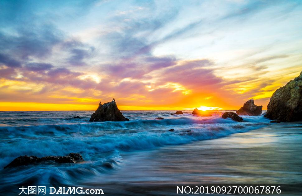 夕阳下海边卷起的海浪和礁石摄影图片