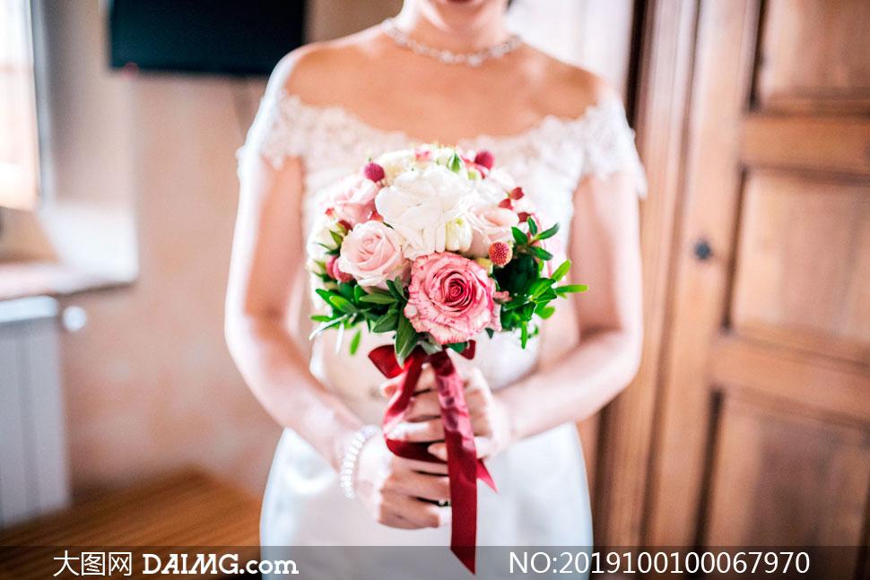 新娘手捧着玫瑰花花束特写摄影图片