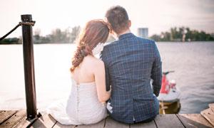 新郎新娘做在木桥上背部摄影图片
