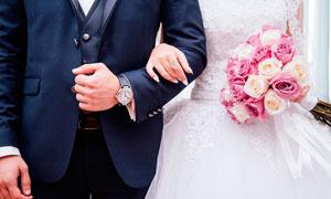 挽着新郎拿着玫瑰花的新娘摄影图片
