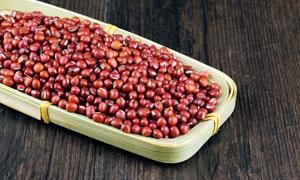 木板上编织盘中装着的红豆摄影图片