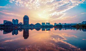 夕阳下的城市建筑和湖泊摄影图片