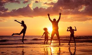 夕阳下海边跳跃的一家四口摄影图片