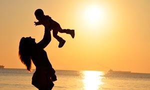 海边妈妈举起宝宝剪影效果摄影图片